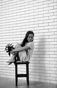 La petite fille est assise sur une chaise et pose devant la caméra