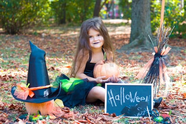 Une petite fille est assise dans un parc avec des feuilles jaunes dans un costume de sorcière. balai, citrouille, masque de chauve-souris, chapeau de sorcière. halloween.