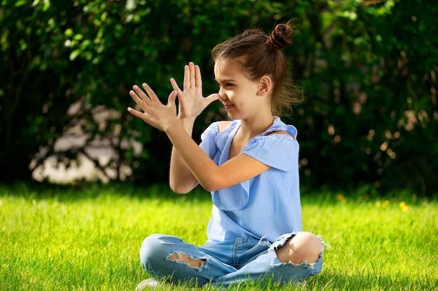 Une petite fille est assise sur l'herbe du parc et montre son nez avec ses mains. photo de haute qualité