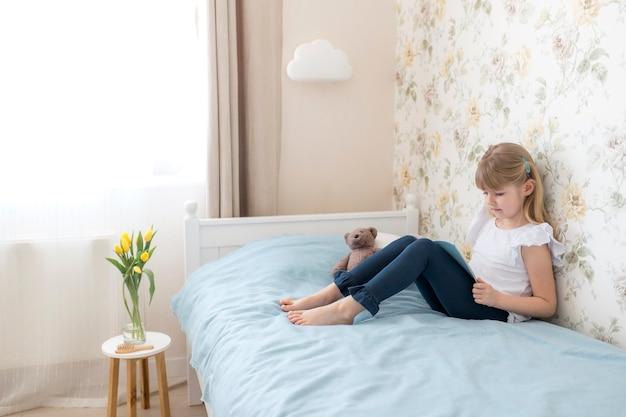 Une petite fille est assise sur le lit dans la chambre élégante et lit un livre bleu. éducation, concept d'enseignement à domicile. faire ses devoirs. tulipes jaunes dans le vase près du lit. applique cloud.