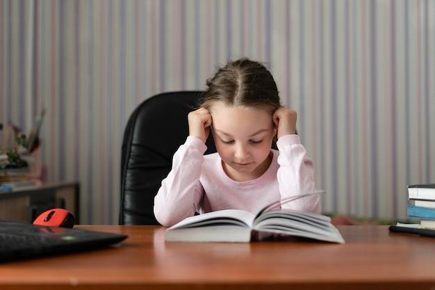Petite fille est assise à la maison et fait ses devoirs.