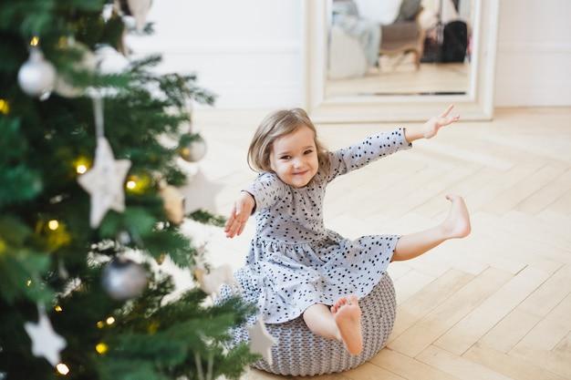 Une petite fille est assise sur un ottoman près de l'arbre de noël, l'intérieur est décoré pour le nouvel an, noël, en attendant les vacances