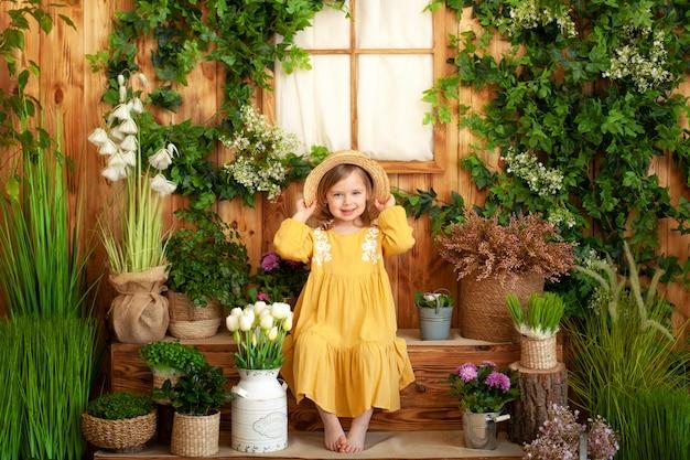Une petite fille est assise sur le porche d'une maison en bois, autour de plantes vertes et de fleurs. l'enfant est en robe jaune, chapeau de paille. concept d'enfance. jardinage. terrasse rustique, véranda. enfant, jouer, arrière-cour