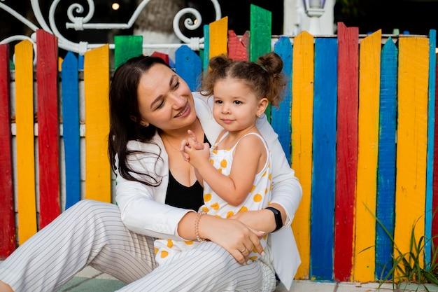 Petite fille est assise près d'une clôture en bois multicolore avec sa mère