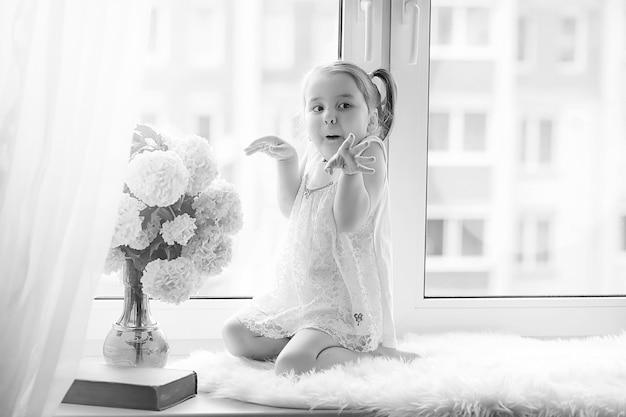 Une petite fille est assise sur le rebord de la fenêtre. un bouquet de fleurs dans un vase près de la fenêtre et une fille reniflant des fleurs. une petite princesse en robe blanche avec un bouquet de fleurs blanches par fenêtre.