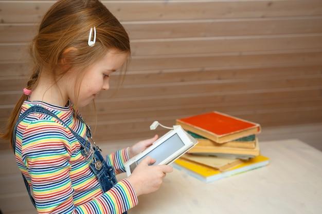 Petite fille est assise à une table et lit un livre électronique.