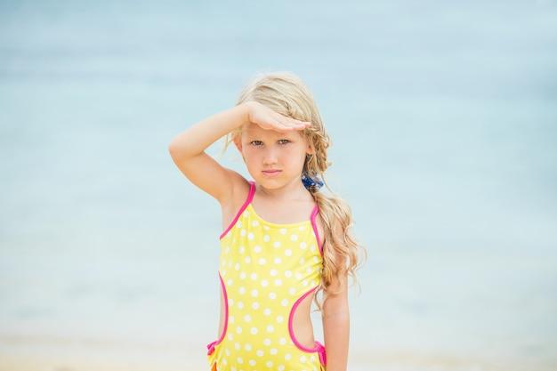 La petite fille est belle et heureuse dans un maillot de bain lumineux l'après-midi sur une plage ensoleillée