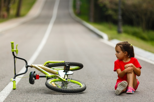 La petite fille est tombée du vélo sur la route