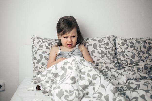 La petite fille est tombée malade. l'enfant a de la fièvre. l'enfant est triste à cause d'un rhume.