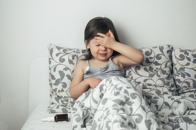 La petite fille est tombée malade. l'enfant a de la fièvre. thermomètre se bouchent.