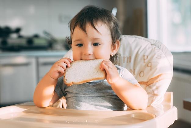 Petite fille est très gourmande en mangeant un morceau de pain blanc, affamée et heureuse