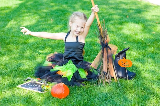 La petite fille est vêtue d'un costume de sorcière, un chapeau noir et du rouge à lèvres noir sur ses lèvres. halloween.