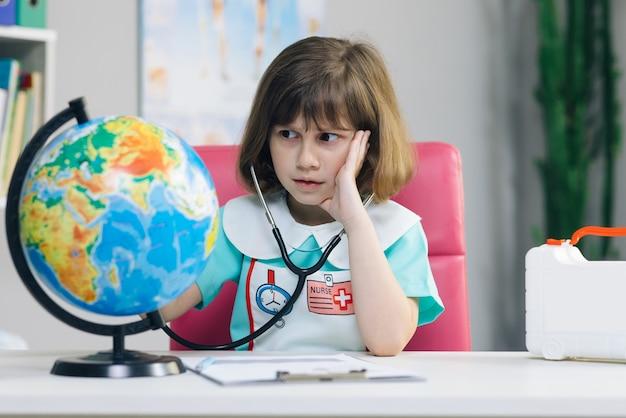 La petite fille est vêtue de vêtements médicaux avec un stéthoscope dans ses mains examine et joue à un jeu de guérison de la planète terre.