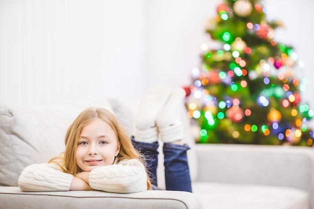 La petite fille était allongée sur le canapé près du sapin de noël