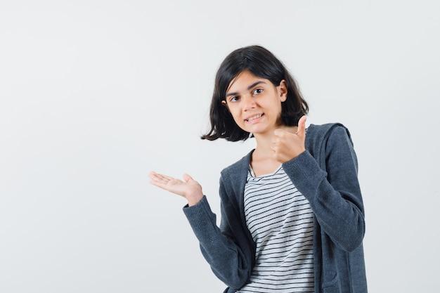 Petite fille étalant la paume de côté, montrant le pouce vers le haut en t-shirt, veste et à l'air confiant.