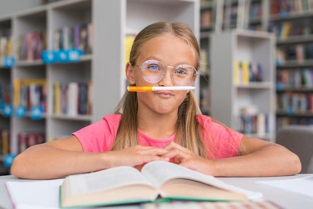 Petite fille étant idiote dans la bibliothèque
