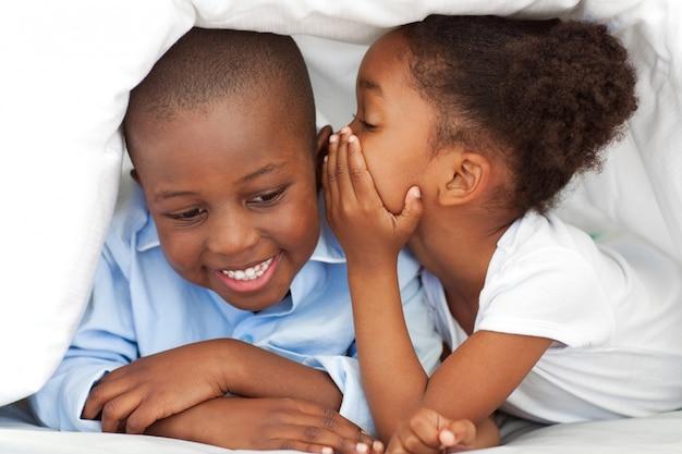 Petite fille ethnique chuchotant quelque chose à son frère