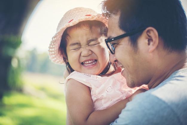 Petite fille étreignant le cou de son papa, père jouant avec la fille heureuse temps en famille.