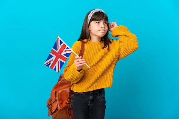 Petite fille étudiant l'anglais isolée sur fond bleu ayant des doutes et pensant
