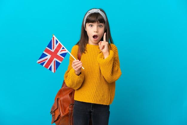 Petite fille étudiant l'anglais isolée sur fond bleu dans l'intention de réaliser la solution tout en levant un doigt vers le haut
