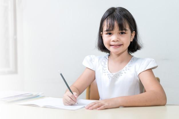 Petite fille étudiante écrivant sur un ordinateur portable à faire ses devoirs et à étudier soi-même à la maison