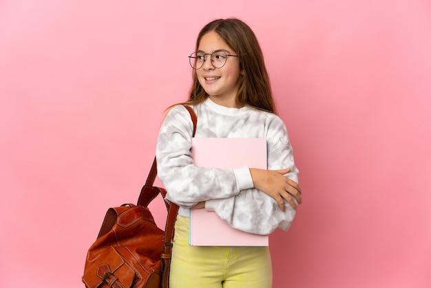 Petite fille étudiante sur fond rose isolé regardant sur le côté et souriant