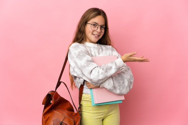 Petite fille étudiante sur fond rose isolé tendant les mains sur le côté pour inviter à venir