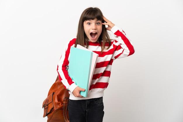 Petite fille étudiante isolée sur fond blanc avec une expression de surprise