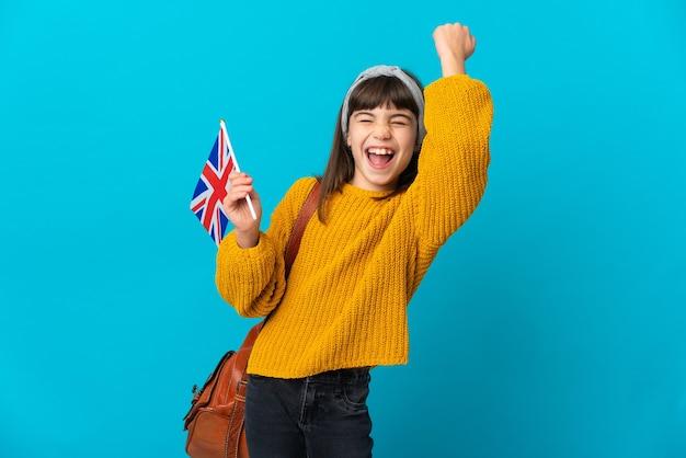 Petite fille étudie l'anglais isolé sur fond bleu célébrant une victoire