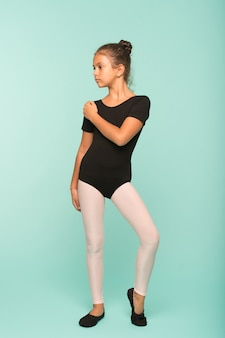 Petite fille étudie la danse à l'école de danse. petite fille a une leçon de danse. grâce et beauté. elle est en parfaite forme.