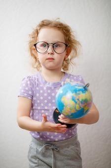 Une petite fille étudie le globe. concept d'éducation