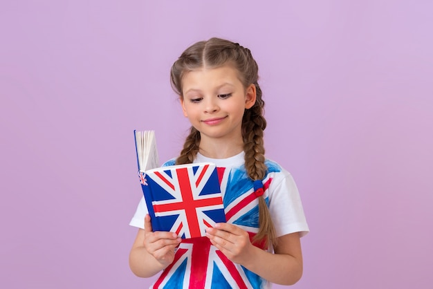 Une petite fille étudie un manuel d'anglais.