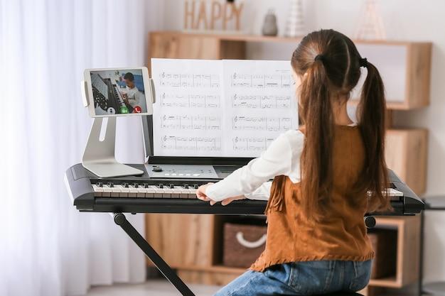 Petite fille étudie la musique avec son ami en ligne à la maison