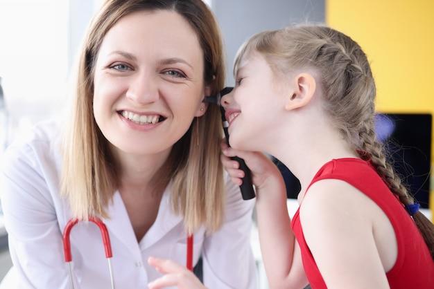 Petite fille examinant l'oreille du médecin en clinique. diagnostic et traitement des maladies de l'oreille chez les enfants concept