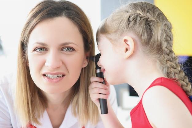 Une petite fille examine l'oreille avec un otoscope pour un test auditif de femme médecin chez les enfants et les adultes
