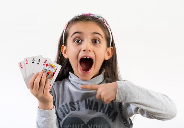 Petite fille excitée avec une main gagnante au poker