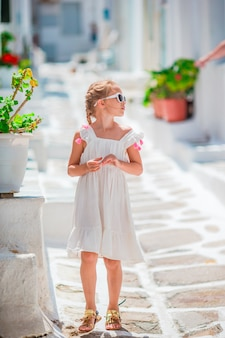 Petite fille à l'extérieur dans le vieux village grec. enfant dans la rue d'un village traditionnel grec typique avec des murs blancs et des portes colorées à mykonos