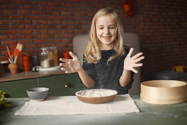 Petite fille faire cuire la pâte pour les cookies