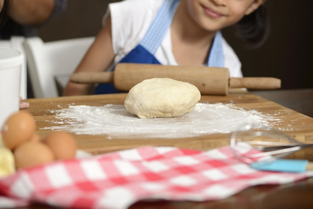 Petite fille à faire de la pâte