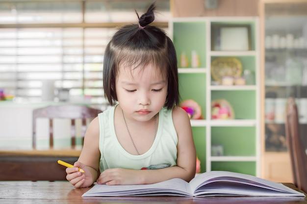 Petite fille à faire ses devoirs pour l'école sur le bureau à la maison