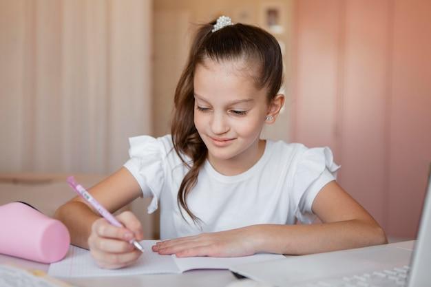 Petite fille en faisant attention aux leçons en ligne à la maison