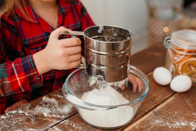 Petite fille faisant des biscuits de noël