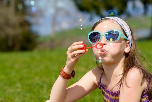 Une petite fille faisant des bulles de savon