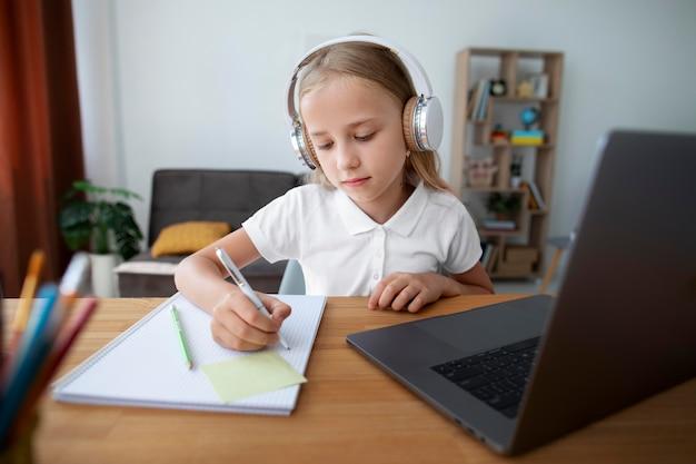 Petite fille faisant des cours en ligne à domicile