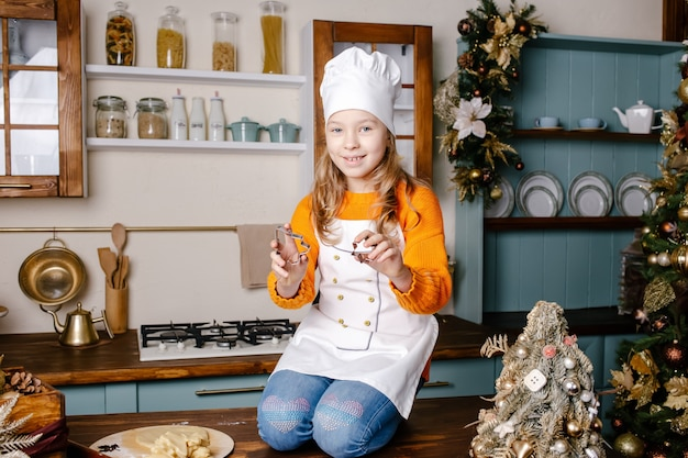 Petite fille faisant du pain d'épice de noël à la cuisine dans un salon décoré de cuisson et de cuisine avec des enfants pour noël à la maison