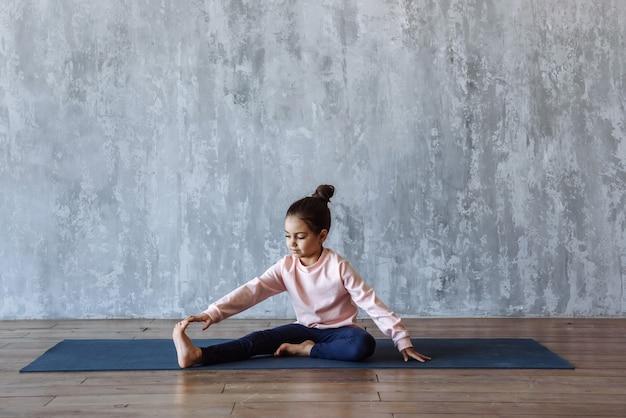 Petite fille faisant du yoga sur le tapis dans la salle de sport, pratiquant des étirements