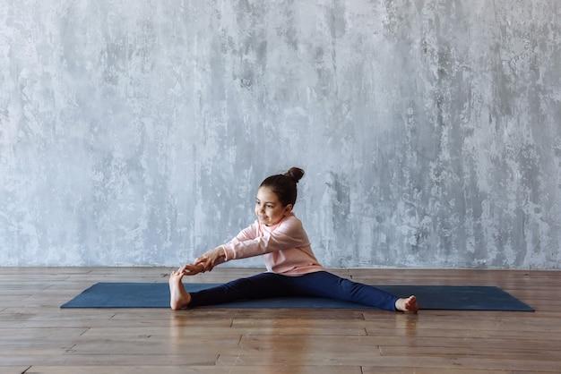 Petite fille faisant des étirements et de la gymnastique sur le sol assis sur le tapis