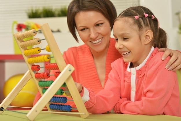 Petite fille faisant des exercices de maths avec sa mère à la maison