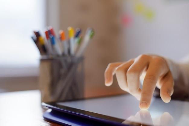 Petite fille faisant des exercices scolaires sur un grand écran d'un pavé tactile