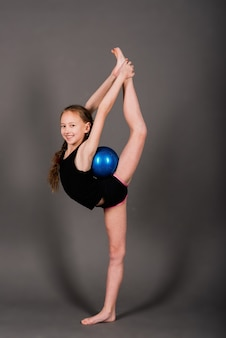 Petite fille faisant de la gymnastique avec cerceau, ballon et split isolé sur fond gris, studio